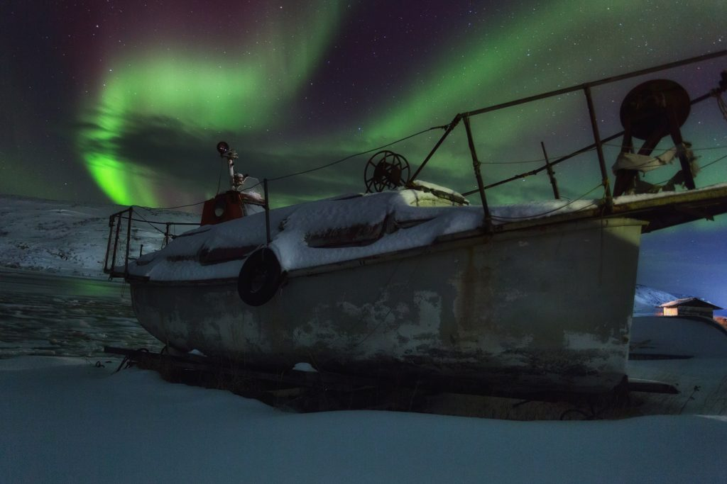 Murmansk Old ship on the background of aurora borealis